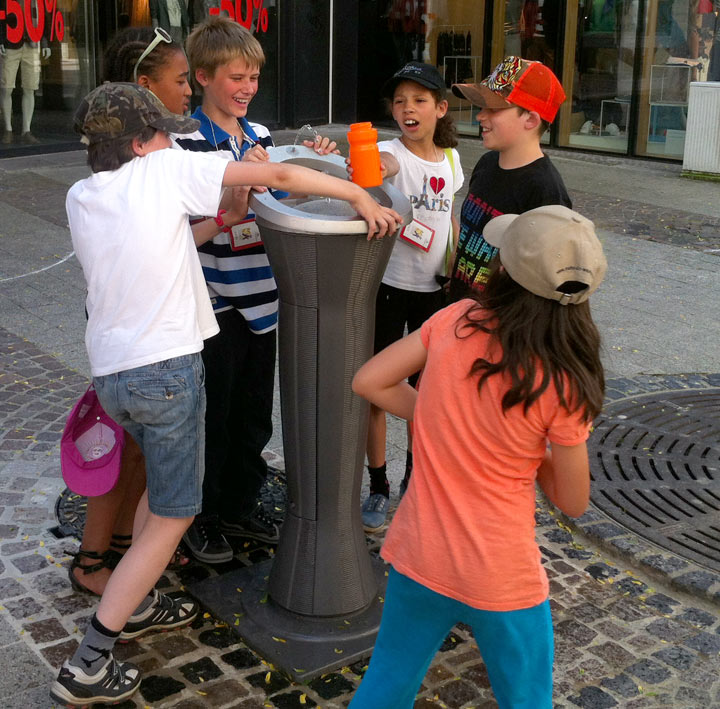Kids drinking from water fountain in Luxembourg city